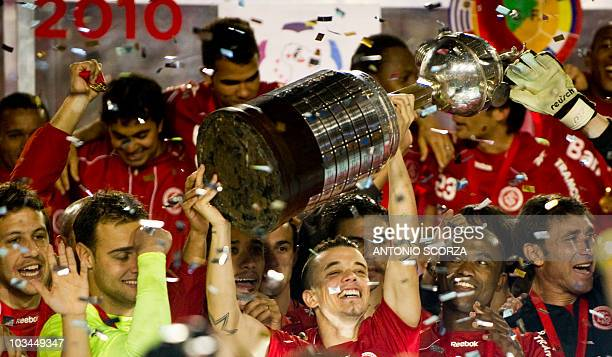 Argentine Internacional forward D'Alesandro holds the Libertadores Cup with teammates after defeating Mexico's Chivas 32 on August 18 2010 in their...