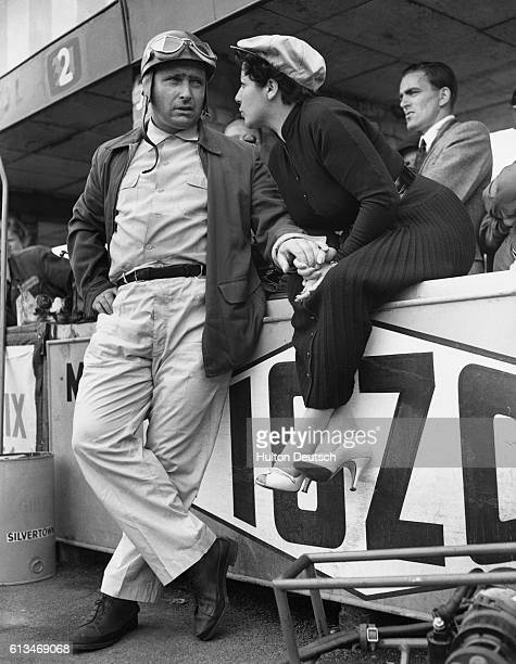 Argentine Juan Manuel Fangio the fivetime world motor racing champion talks to his wife at the Silverstone racing circuit in Northamptonshire where...
