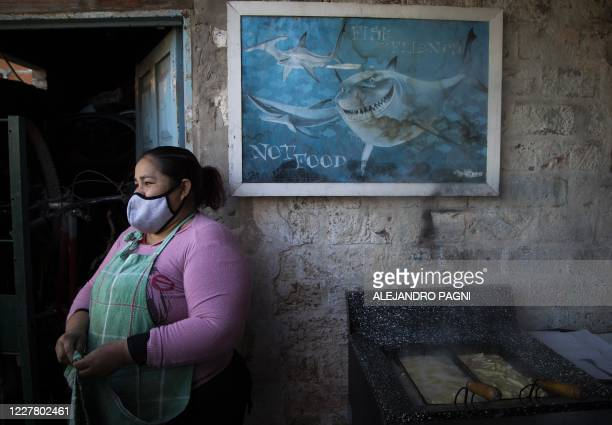 Argentine Judith gestures while preparing french fries for sale at her own store in the Padre Carlos Mugica neighborhood also known as Villa 31...