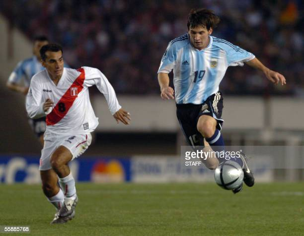 Argentine Lionel Messi vies for the ball with Peruvian Rainer Torres 09 October 2005 at the Monumental stadium in Buenos Aires Argentina during their...