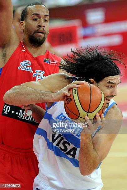 Argentine Luis Scola vies for the ball with Puerto Rican Ricardo Sanchez during their Spain 2014 FIBA World Cup qualifier game in Caracas on...