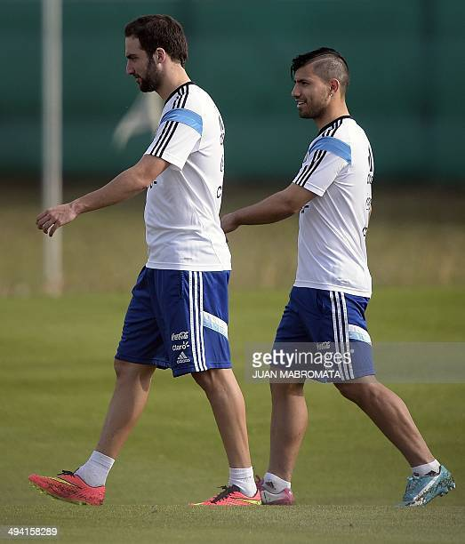 Argentine national football forwards Gonzalo Higuain and Sergio Aguero leave the field after a training session at the squad's training complex in...