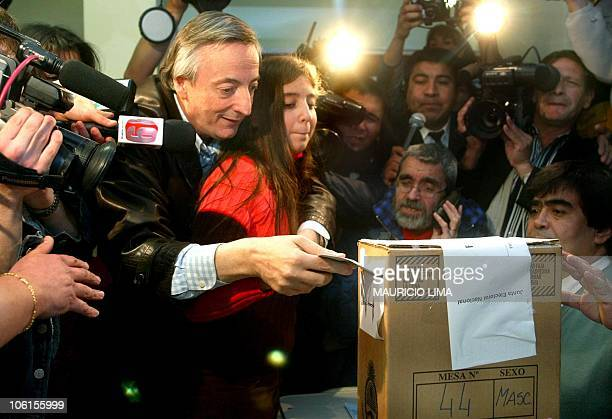 Argentine Peronist presidential candidate Néstor Kirchner with his daughter Florencia deposits his ballot 27 April 2003 at a public school being used...