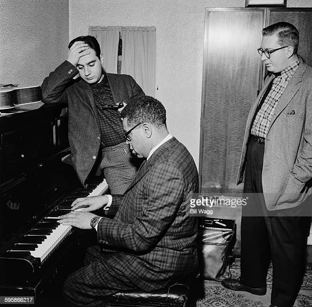 Argentine pianist composer and arranger Lalo Schifrin and American drummer Mel Lewis listen to American jazz trumpeter Dizzy Gillespie on the piano...