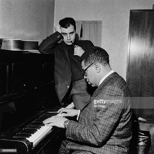 Argentine pianist composer and arranger Lalo Schifrin listens to American jazz trumpeter Dizzy Gillespie on the piano circa 1960
