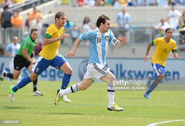 Argentine player Lionel Messi Brazilian players Bruno Uvini and Romulo chase after the ball during the friendly match Argentina against Brazil at the...