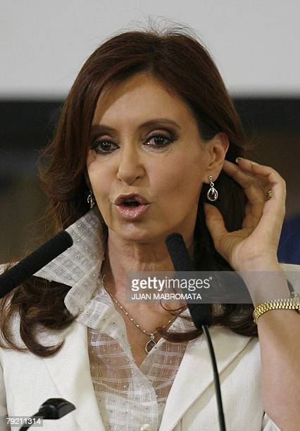 Argentine President Cristina Kirchner shows the earrings and necklace made with Bolivian stones and silver, received as a gift from Bolivian...