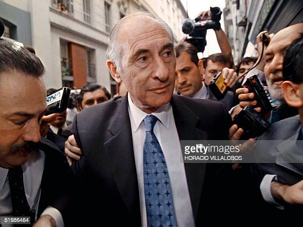 Argentine President Fernando de la Rua is surrounded by journalists 19 December 2001 in Buenos Aires after a march against economic austerity...