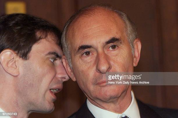 Argentine President Fernando de la Rua listens to an aide at news conference in Washington