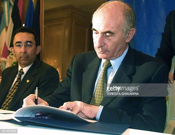 Argentine President Fernando de la Rua signs a declaration 04 December 2000 as Carlos Quintanilla vice president of El Salvador watches in San Jose...