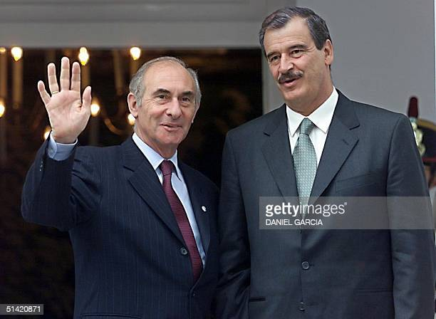 Argentine President Fernando de la Rua waves at the media as he meets with Mexican Presidentelect Vicente Fox 08 August 2000 at the presidential...