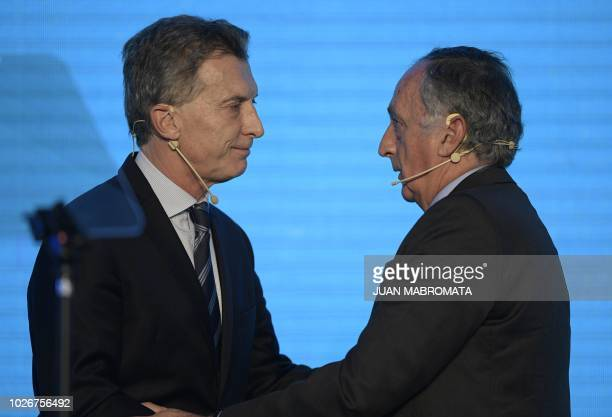 Argentine President Mauricio Macri and the president of Argentine Industrial Union Miguel Acevedo shake hands during the closing ceremony of the...