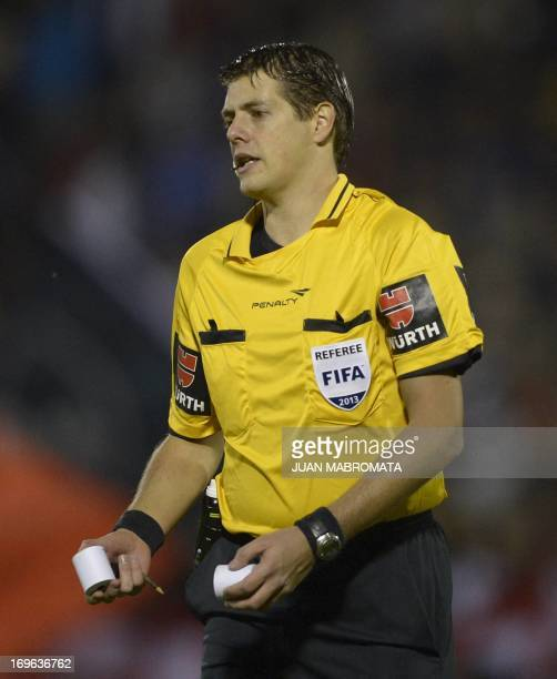 Argentine referee German Delfino holds paper rolls during the Copa Libertadores 2013 quarterfinals second leg football match between Newell's Old...