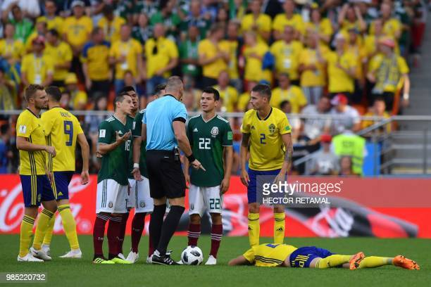 Argentine referee Nestor Pitana presents Mexico's defender Jesus Gallardo with a yellow card during the Russia 2018 World Cup Group F football match...