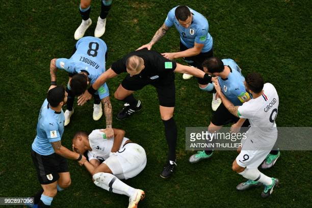TOPSHOT Argentine referee Nestor Pitana separates players during the Russia 2018 World Cup quarterfinal football match between Uruguay and France at...