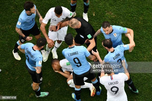 Argentine referee Nestor Pitana separates players during the Russia 2018 World Cup quarterfinal football match between Uruguay and France at the...
