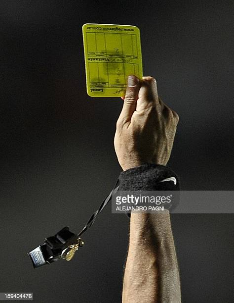 Argentine referee Patricio Loustau shows a yellow card during their South American U20 Championship Group B football match between Uruguay and Brazil...