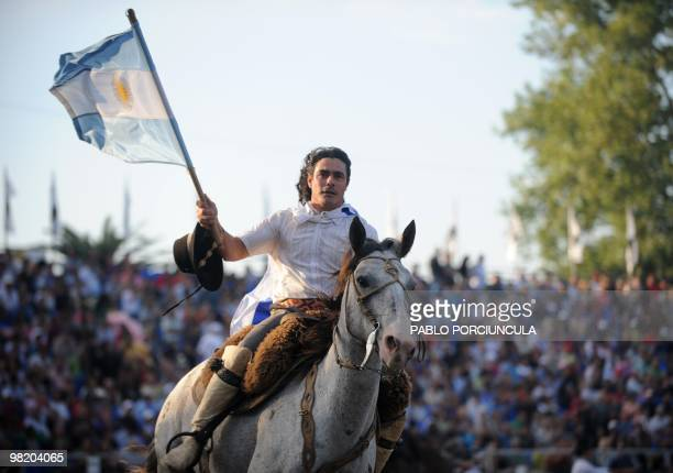 Argentine rider Miguel Diaz carries an Argentine national flag on a lap of honour following a rodeo at the Patria Grande, a festival held every...