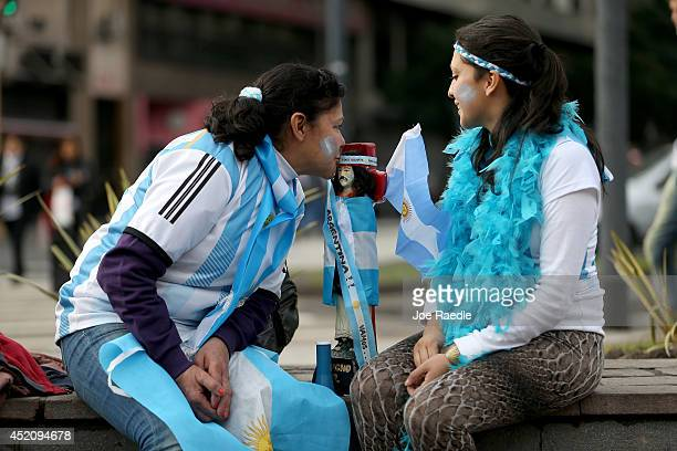 Argentine soccer fans Anna Baez and Deborah Chanal sit with Santo Gauchito Gil as they hope he helps their team win the World Cup final on July 13...