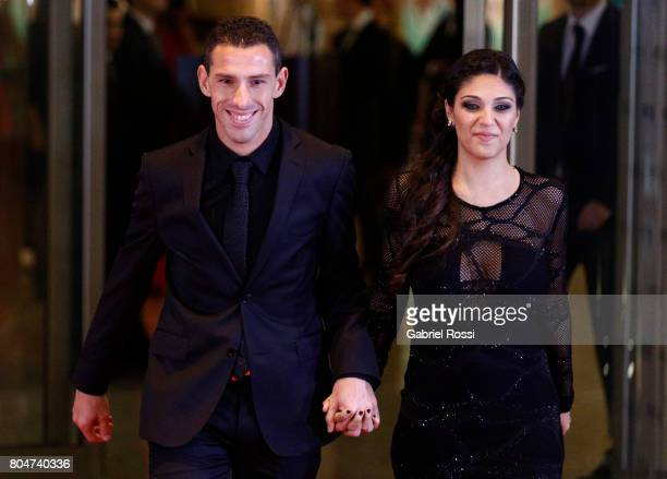 Argentine soccer player Maximiliano Rodríguez and his wife Gabriela Rodriguez pose for pictures on the red carpet during Lionel Messi and Antonela...