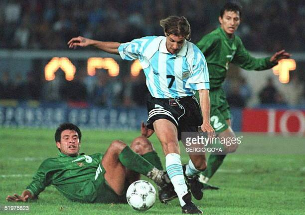 Argentine soccer star Claudio Caniggia takes the ball from Bolivian defenders Angel Paraba and Juan Pena 24 April in Buenos Aires during their World...