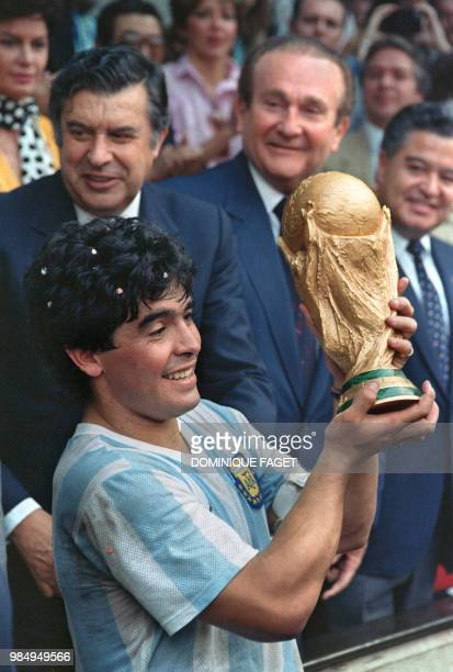 Argentine soccer star team captain Diego Armando Maradona displays the World Soccer Cup won by his team after a 3-2 victory over West Germany 29 June...