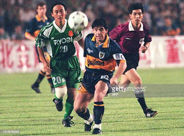Argentine soccer superstar Diego Maradona passes the ball to his Boca Junior teammate as a Beijing Guoan unidentified player and the referee look on...