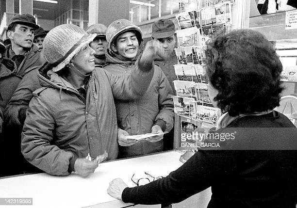 Argentine soldiers buy postcards at a souvenir shop in Stanley 13 April 1982 Twentyfive years after the Falklands / Malvinas war Argentina continues...
