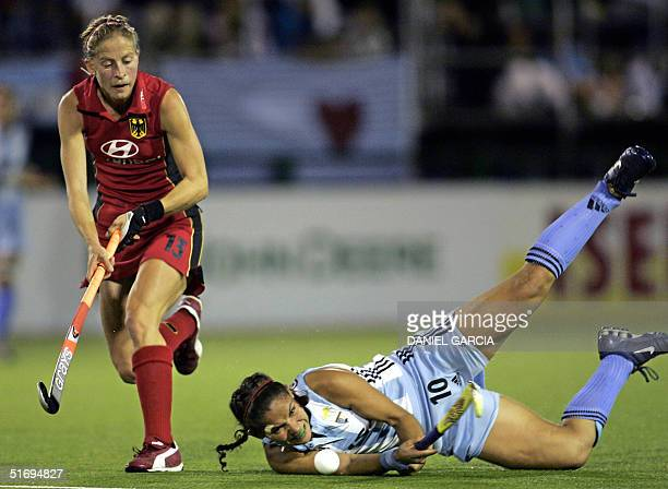 Argentine Soledad Garcia falls down while trying to control the ball in front of German Marion Rodewald during the field hockey match of the...