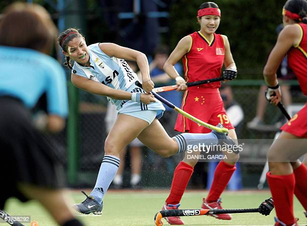 Argentine Soledad Garcia hits the ball between Chinese Chen Quiqi and Huang Xuejiao and umpire Kazuko Yasueda during the field hockey match for the...