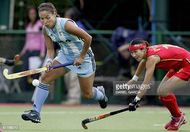 Argentine Soledad Garcia tries to past Chinese Chen Quiqi during a field hockey match for the Champions Trophy in Rosario Argentina 13 November 2004...