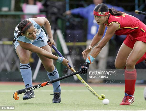 Argentine Soledad Garcia tries to past Chinese Qiu Yingling during the field hockey match for the Champions Trophy in Rosario Argentina 13 November...