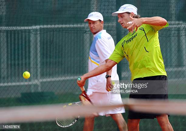 Argentine tennis player David Nalbandian hits a return while captain Martin Jaite looks on during the practice at the auxiliary court of Parque Roca...