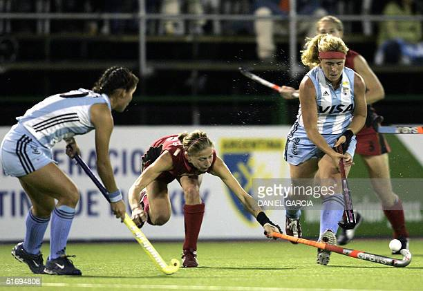 Argentine Vanina Oneto battles for the ball with German Marion Rodewald while teammate Soledad Garcia looks on during the field hockey match at the...