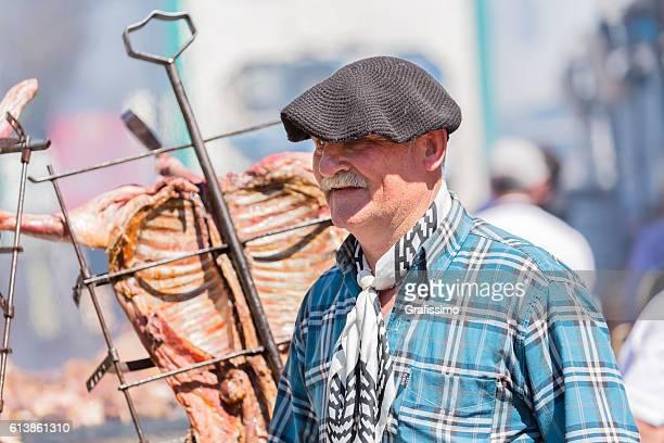 argentinean asado (bbq) old gaucho controlling goat - carne assada imagens e fotografias de stock