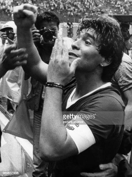Argentinean captain and goalgetter Diego Maradona soaking wet from heavy rains gestures wildly towards a group of photographers after the end of the...