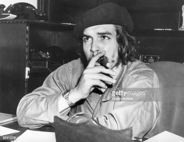 Argentineborn Cuban revolutionary leader and economic advisor Ernesto 'Che' Guevara sits at a desk and smokes a cigar wearing military fatigues and a...