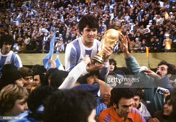 Argentine's national soccer team captain Daniel Passarella holds the World Cup trophy as he is carried on the shoulders of fans after Argentina...
