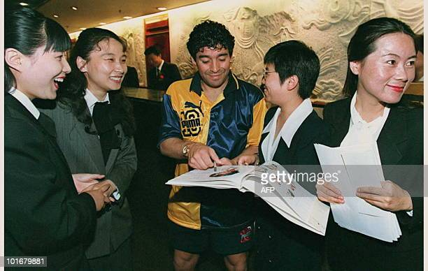 Argentine's soccer superstar Diego Maradona delights his Chinese fans as he signs autographs for a group of hotel receptionists in Beijing 24 July...