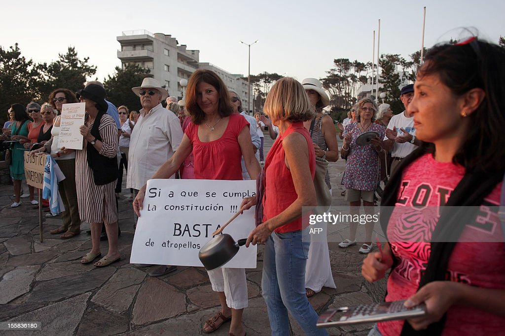 Argentines take part in a 'cacerolazo' to protest against the possible reelection of President Cristina Fernandez de Kirchner and the growing insecurity, corruption and restrictions on the purchasing of US dollars, in the Uruguayan seaside resort of Punta del Este, 135 km east of Montevideo, on November 8, 2012. Thousands of opponents of Fernandez de Kirchner gathered in the Argentine capital Buenos Aires and other cities across the world banging their cooking pots in a noisy protest against any possible bid she might run for a third term. 'Say no to reelection,' said the call to protest which was sent across the country via social media websites. Fernandez, 59, is currently barred by the Argentine Constitution from running for a third consecutive term, but her supporters in the Congress have been lobbying for a constitutional amendment.