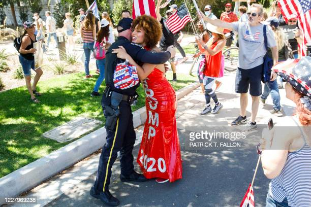 Argentine-US singer Joy Villa hugs a Beverly Hills police officer as people march in support of the US president during a WalkAway rally on August 8,...