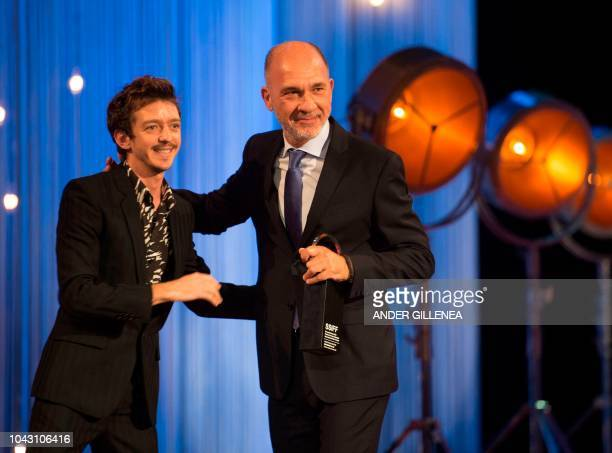 Argentinian actor Dario Grandinetti receives his 'Concha de Plata' best actor award for his role in the film 'Rojo' from Argentinian actor Nahuel...