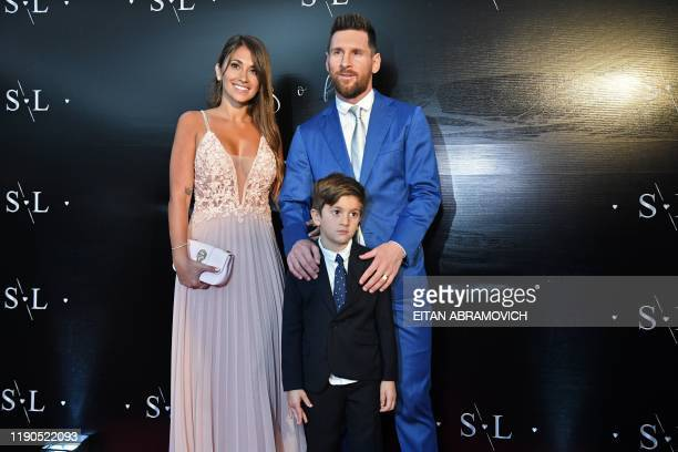 TOPSHOT Argentinian Bolcelona forward Lionel Messi poses with his wife Antonella Roccuzzo and their son Thiago upon their arrival at a party thrown...