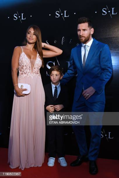 Argentinian Bolcelona forward Lionel Messi poses with his wife Antonella Roccuzzo and their son Thiago upon their arrival at a party thrown by...