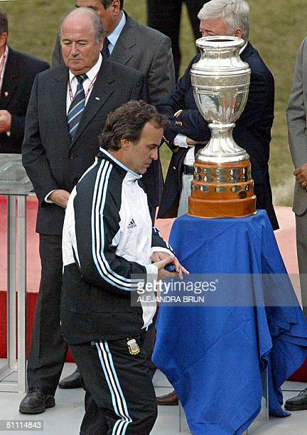 Argentinian coach Marcelo Bielsa passes by Joseph Blatter and the Copa America 2004 trophy at the end of the final match against Brazil in Lima Peru...