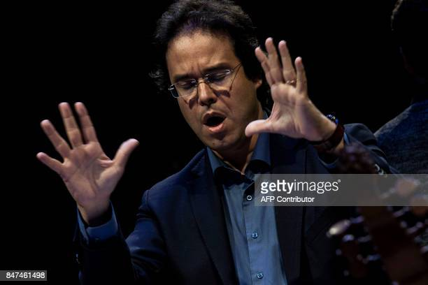 Argentinian conductor Leonardo Garcia Alarcon leads a baroque orchestra on September 15 2017 in the cathedral in Ambronay during a rehearsal prior to...
