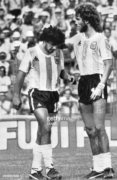 Argentinian defender Alberto Tarantini comforts midfielder Diego Maradona as he walks off the field after being sent off by Mexican referee Mario...