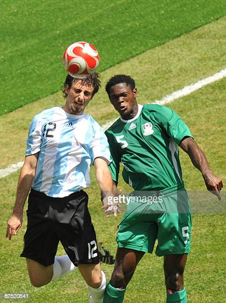 Argentinian defender Nicolas Pareja and Nigerian defender Dele Adeleye jump for the ball during the men's Olympic football final Argentina vs Nigeria...