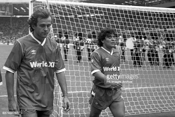 Argentinian Diego Maradona and Michel Platini walk off the pitch after their Rest of the World XI side lost 1-0