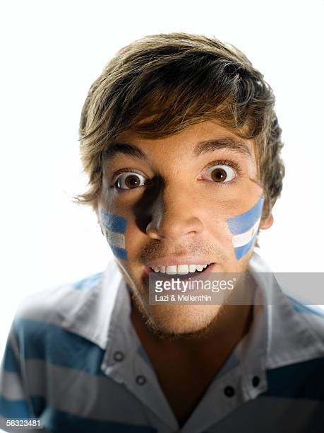 Young man with eyes open wide, Argentinean face paint, close-up